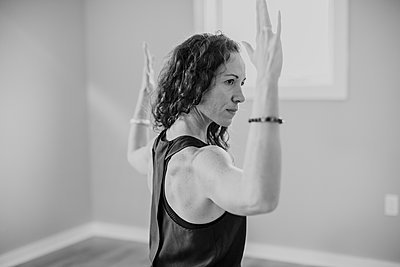 black and white picture of woman concentrating while doing yoga - p1166m2153750 by Cavan Images