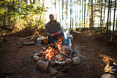 Man warming by the fire at sunset while car camping in coastal Maine - p1166m2216846 by Cavan Images