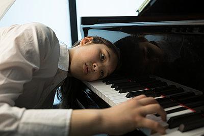 Adorable schoolgirl playing piano in music school - p1315m2003044 by Wavebreak