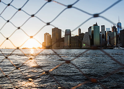 USA, Brooklyn, view to Manhattan through fence at twilight - p300m1205426 by Uwe Umstätter