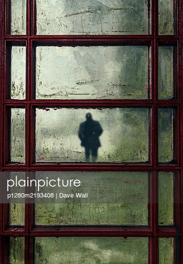 Man fleaing through dirty windows telephone box - p1280m2193408 by Dave Wall