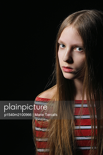 long-haired teenage girl with striped sweater on black background - p1540m2100966 by Marie Tercafs