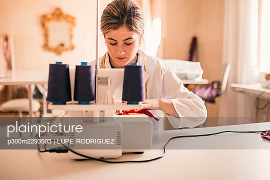 Female dressmaker using sewing machine while sitting at workbench - p300m2293503 by LUPE RODRIGUEZ