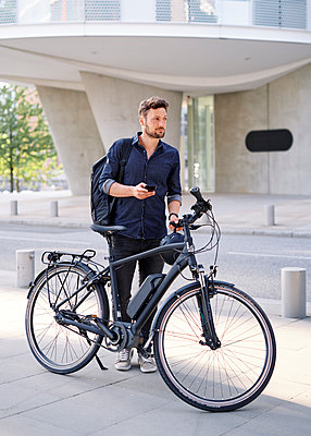 Bicycle courier using smartphone - p1124m2052988 by Willing-Holtz