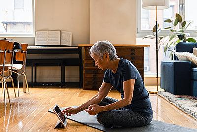 Senior woman using digital tablet while exercising in living room - p1166m2285604 by Cavan Images