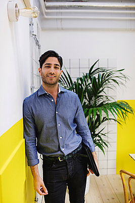 Portrait of confident young man leaning on wall in creative office - p426m1407160 by Maskot