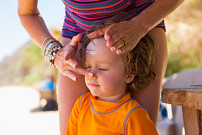 Caucasian mother applying sunscreen to face of son - p555m1305359 by Marc Romanelli