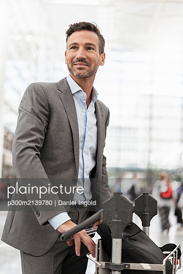 Businessman with luggage cart atb the airport - p300m2139780 by Daniel Ingold