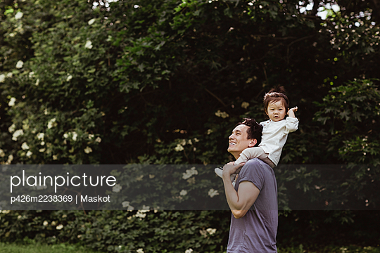 Cheerful father carrying male toddler on shoulder by plants at park - p426m2238369 by Maskot