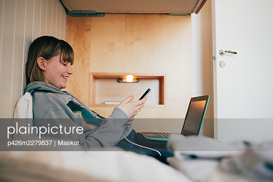 Smiling girl text messaging through mobile phone while sitting on bed at vacation home - p426m2279837 by Maskot