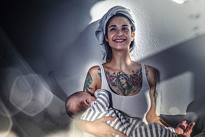Smiling tattooed young woman holding her baby at home - p300m2132388 by Richárd Bellevue