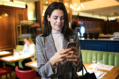 Businesswoman using cell phone in a restaurant - p300m2140674 by Josep Suria