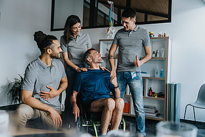 Smiling male patient looking at physical therapist gesturing by colleagues in practice - p300m2275901 by Mareen Fischinger