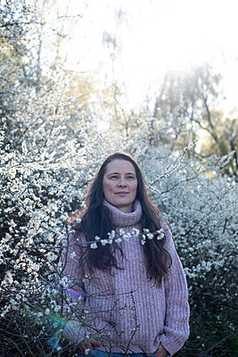 Woman standiing in blooming blackthorn - p310m2279012 by Astrid Doerenbruch