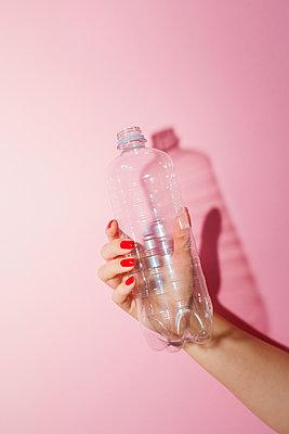Frau hält leere Plastikflasche in der Hand - p432m2119397 von mia takahara