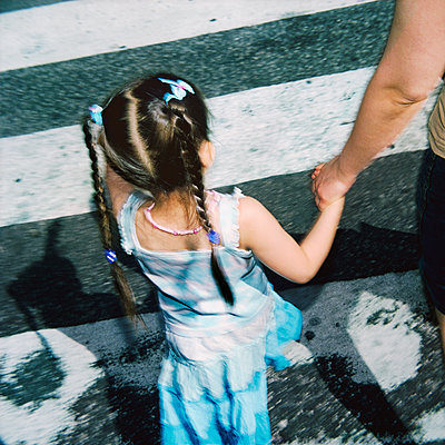 Mother And Daughter Hold Hands At The Crossroad, Stockholm  - p847m1529297 by Mikael Andersson