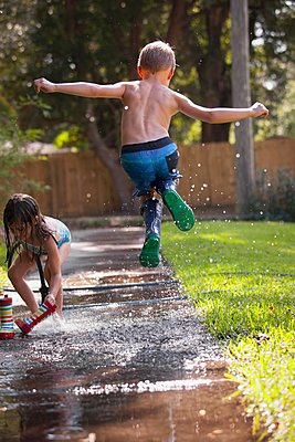 Boy in wellies jumping in mid-air on sidewalk - p924m1125736f by Kinzie Riehm