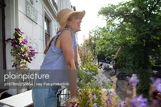 Blonde woman on her balcony - p1678m2258854 by vey Fotoproduction