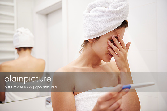 Young woman in bathroom worrying over pregnancy test result - p300m2041655 von gpointstudio