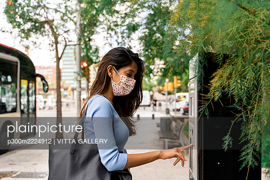 Woman in face mask purchasing bus ticket during COVID-19 - p300m2224912 by VITTA GALLERY
