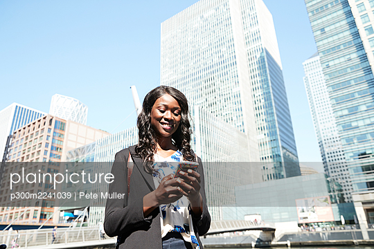Smiling businesswoman using mobile phone in city on sunny day - p300m2241039 by Pete Muller