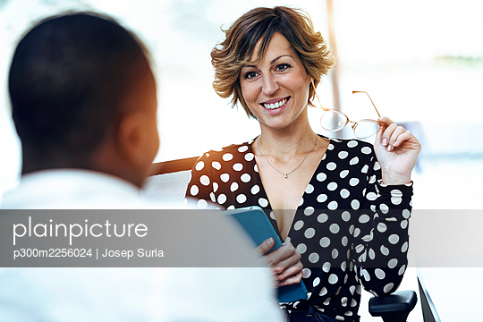 Smiling young businesswoman looking at businessman during meeting in coworking office - p300m2256024 by Josep Suria