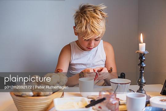 Boy having breakfast - p312m2092172 by Peter Rutherhagen