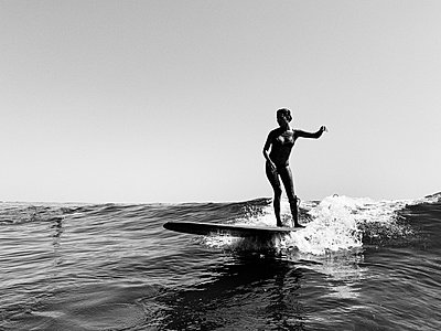 A female surfer in a bikini rides a small wave, black and white - p1166m2108275 by Cavan Images