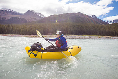 Explorer enjoying a sunny day rafting ,kayaking in the rocky mountains - p1166m2213520 by Cavan Images