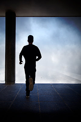 Man Silhouette Running in Underpass  - p1248m2092504 by miguel sobreira