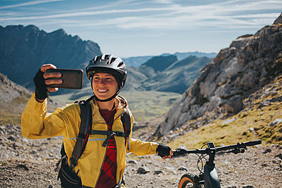 Smiling female cyclist taking selfie with mountain bike against mountain, Picos de Europa National Park, Cantabria, Spain - p300m2240183 by David Molina Grande