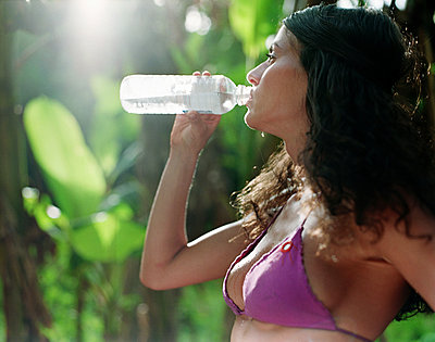 woman in bikini drinking water from plastic bottle - p3160147f by BreBa photography