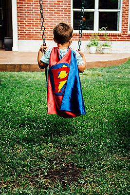 Caucasian boy wearing superhero costume on swing - p555m1304500 by Inti St Clair