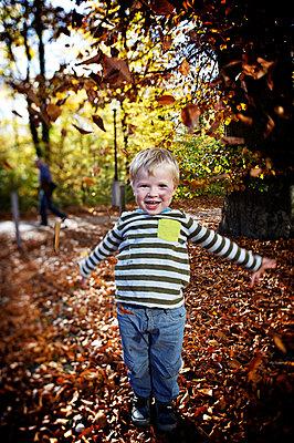 Kleiner Junge spielt mit Laub  - p819m1066375 von Kniel Mess