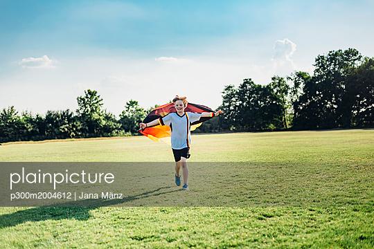 Boy, enthusiastic for soccer world championship, waving German flag - p300m2004612 von Jana Mänz