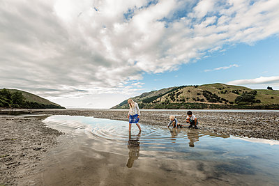 Siblings looking for shellfish on the South Island of New Zealand - p1166m2130651 by Cavan Images