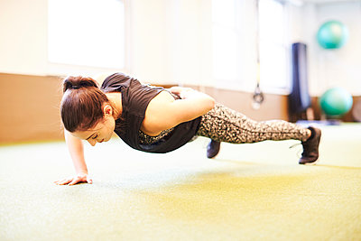 Woman doing one arm push-ups - p343m2046860 by Josh Campbell