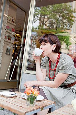 Woman having coffee at sidewalk cafe - p429m665276f by Christine Schneider