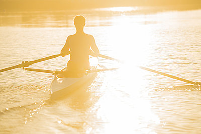 Caucasian man rowing on river at sunset - p555m1303395 by Pete Saloutos