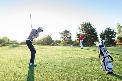 Friend watching man hitting ball on golf course - p555m1472893 by Kolostock