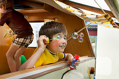 Two boys blowing bubbles out of caravan - p924m664933f by Mieke Dalle