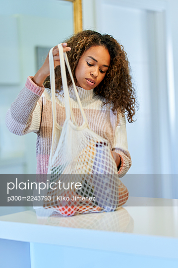 Afro young woman with reusable bag of groceries in kitchen at home - p300m2243793 by Kiko Jimenez