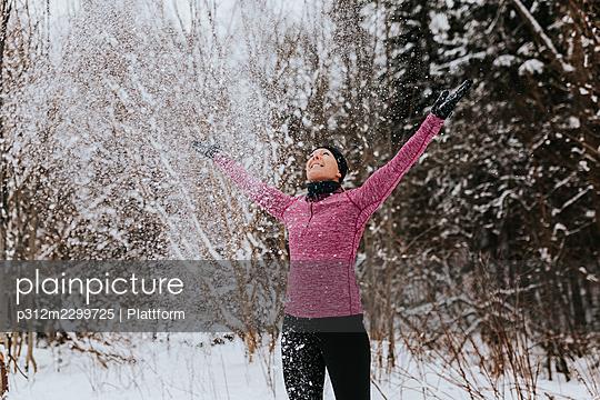 Happy woman throwing snow - p312m2299725 by Plattform
