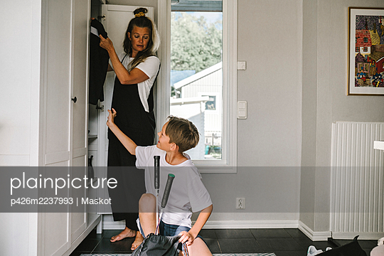 Son talking with mother standing by closet at home - p426m2237993 by Maskot