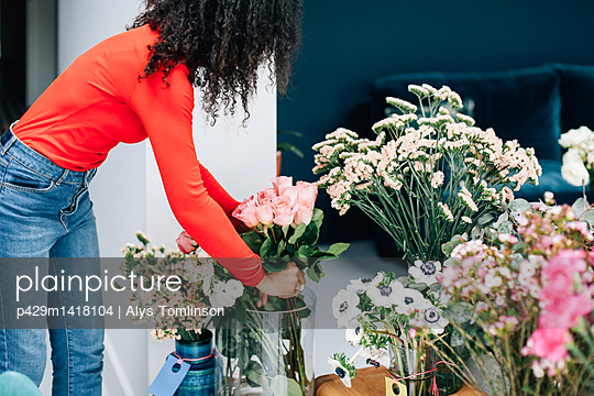 Female florist arranging roses in vase for shop display - p429m1418104 by Alys Tomlinson