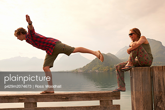 Young couple balancing on pier, Lake Annecy, Annecy, Rhone-Alpes, France - p429m2074673 by Ross Woodhall