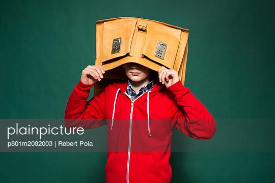 Schüler mit Kopf in seiner Schultasche - p801m2082003 von Robert Pola