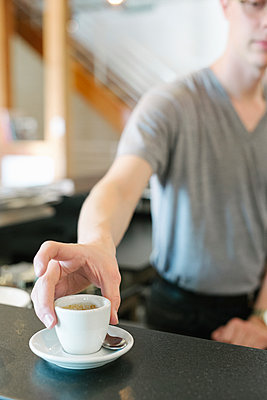 Man standing at a counter in a coffee shop, reaching for a cup of espresso coffee. - p1100m1177741 by Mint Images