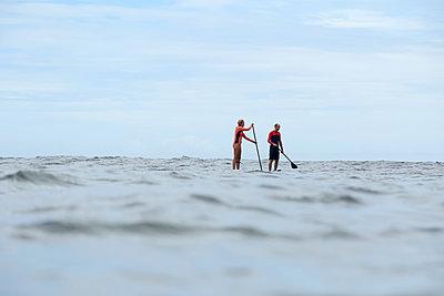 Two sup surfers in ocean - p1166m2136334 by Cavan Images