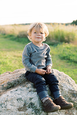Little toddler boy looking proud whilst sitting on a big rock. - p1166m2151879 by Cavan Images